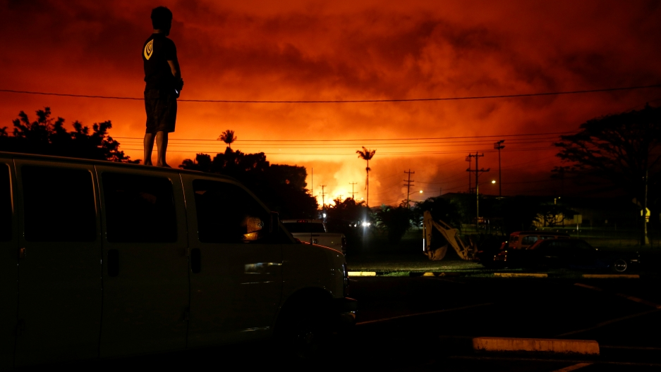 Darryl Sumiki, 52, of Hilo, stands atop a car and watches as lava lights up the sky in bright red above Pahoa during ongoing eruptions of the Kilauea Volcano in Hawaii.