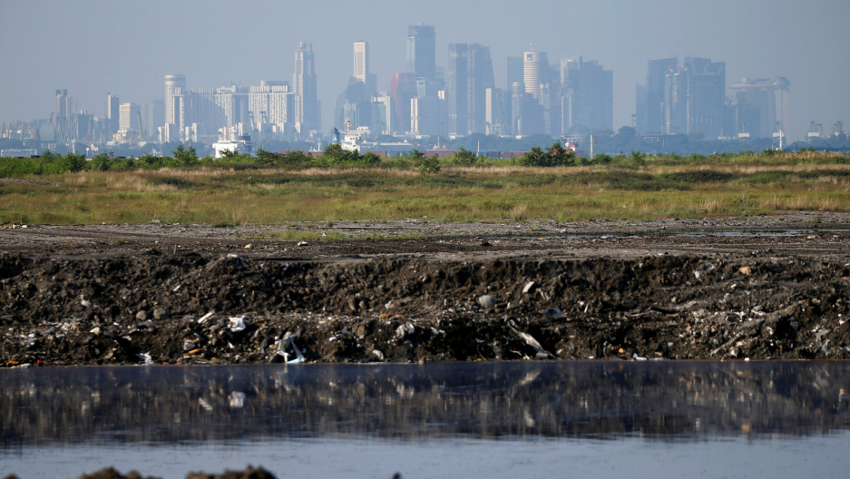 the singapore skyline in the background and a landfill in the foreground