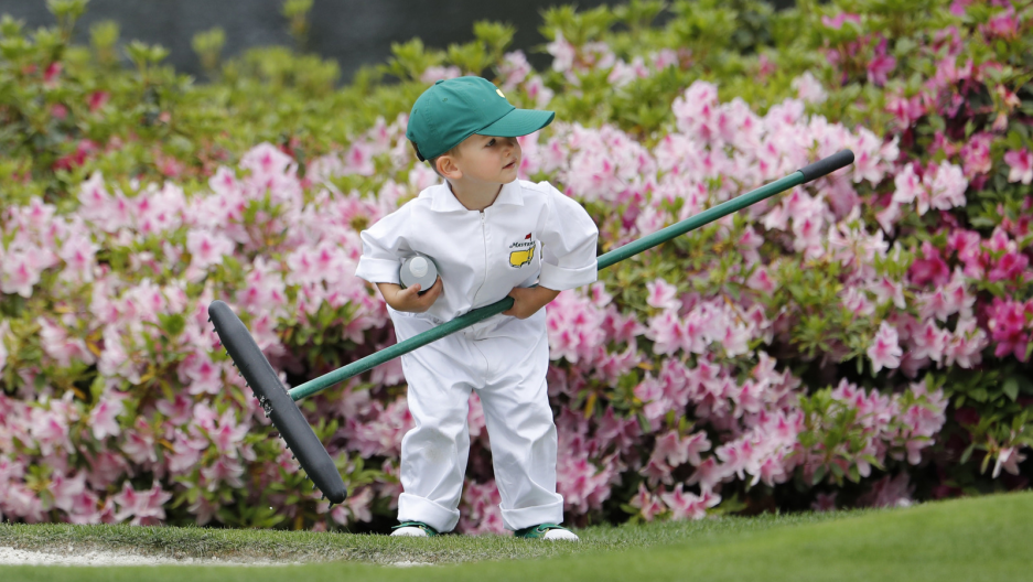 a little boy is dressed in a white gown at a golf event