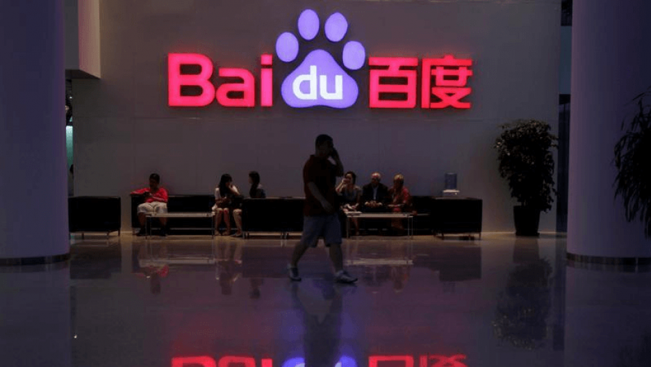 An employee uses his mobile phone as he walks past the company logo of Baidu at its headquarters in Beijing, Aug. 5, 2010.