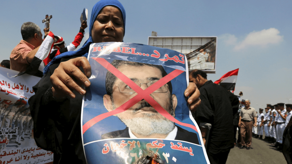 A woman burns a portrait of ousted President Mohamed Mursi at the funeral of Egyptian public prosecutor Hisham Barakat, on the second anniversary of the June 30 protests, in Cairo, Egypt, June 30, 2015.