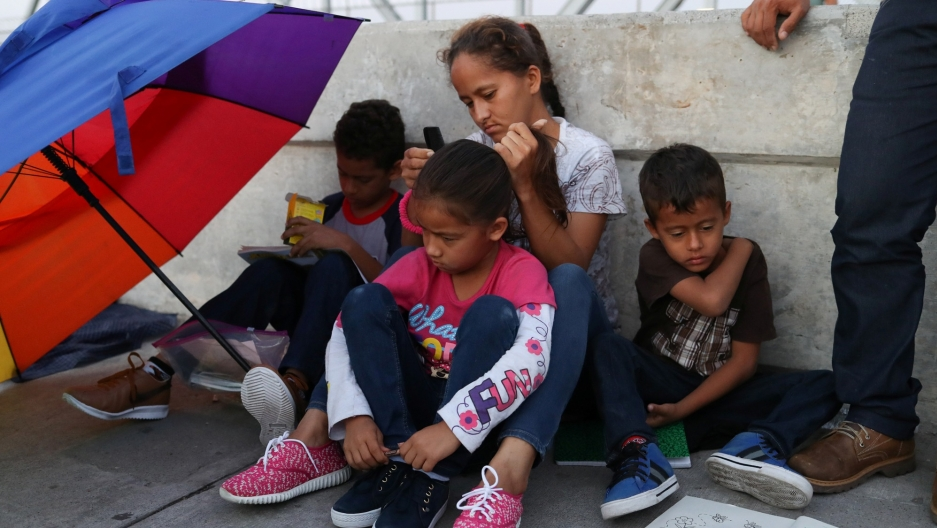 A Honduran family of three children and a mother seeking asylum sit with a colorful umbrella on the Mexican side of the Brownsville-Matamoros International Bridge.