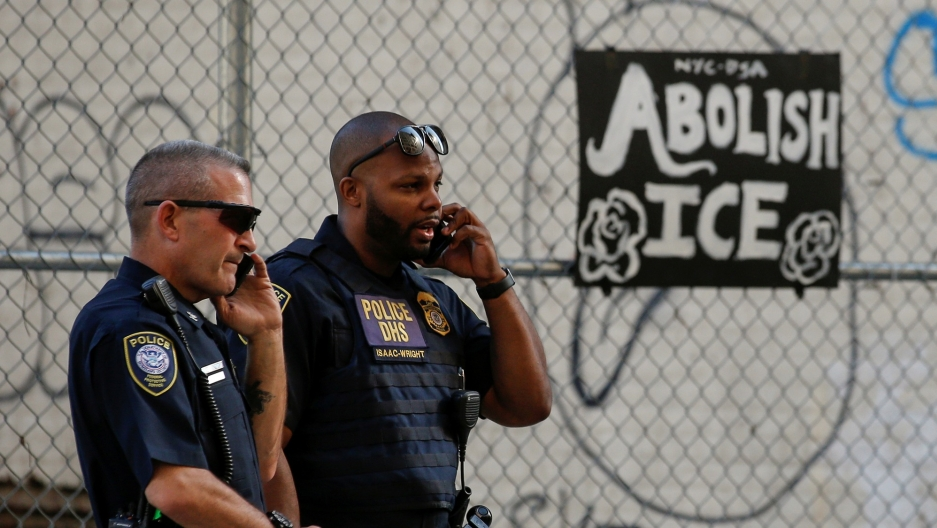 Two uniformed Department of Homeland Security officers are shown looking off to the right of the frame while talking on their walkie-talkies.