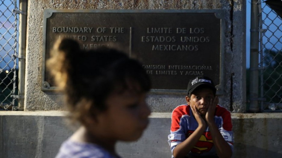 A young Honduran girl walks by in the near ground while a young boy in a Superman shirt and hat sits next to a sign noting the US border.
