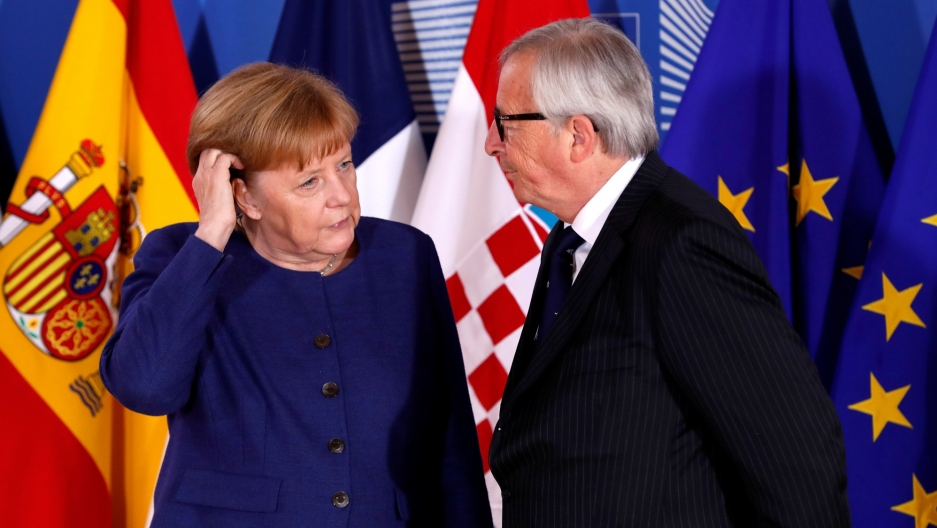 German Chancellor Angela Merkel is seen in a blue dress next to European Commission President Jean-Claude Juncker in a blue suit with several flags behind them.