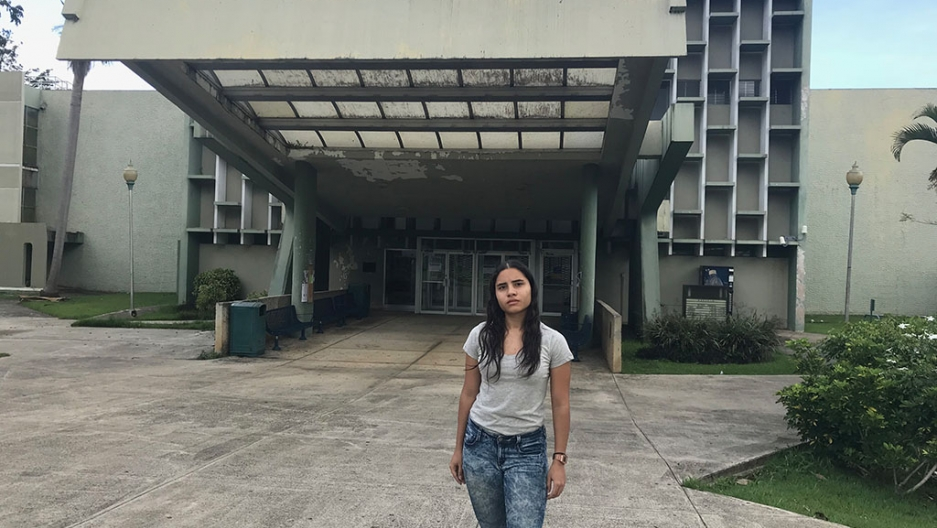 A young woman stands in front of a gray building.