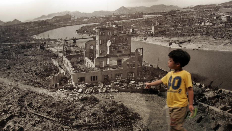 A boy looks at a photograph showing Hiroshima city after the 1945 atomic bombing, at the Hiroshima Peace Memorial Museum, Japan, Aug. 6, 2007.