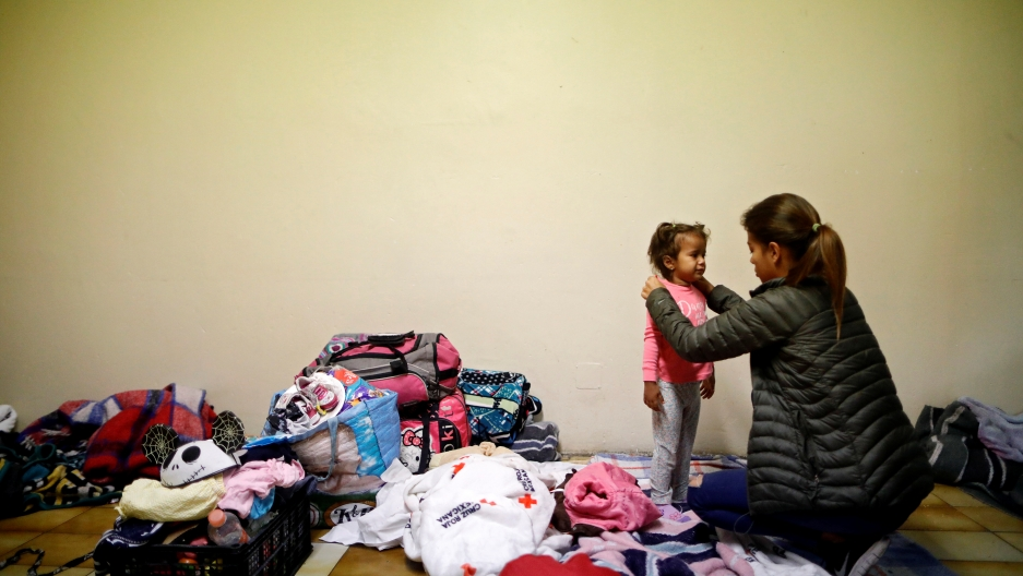 A woman dresses a girl at a shelter, surrounded by luggage and clothes