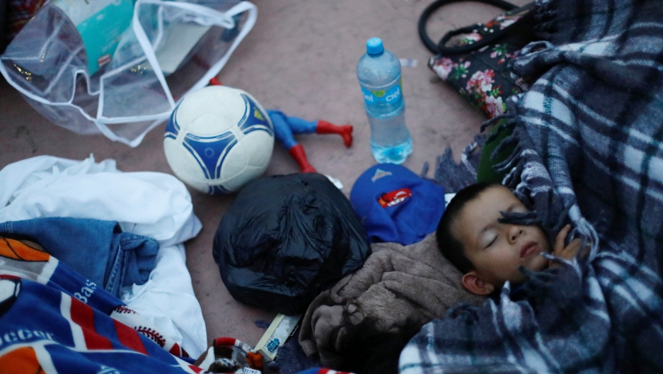 A child traveling with a caravan of migrants from Central America sleeps