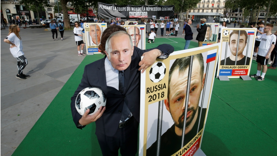 An activist with Reporter Without Borders, wearing a mask depicting Russian President Vladimir Putin, stands next to a giant portrait of imprisoned Russian journalist Alexei Kungurov on the Place de la Republique