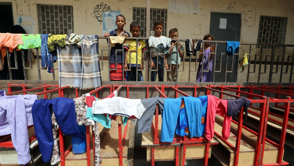 Children stand behind a fence at a school to which they have been evacuated from a village near Hodeidah airport amid fighting between government forces and Houthi fighters in Hodeidah,