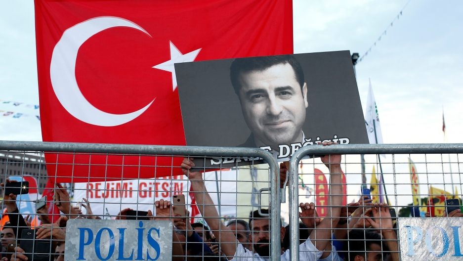 A supporter of Turkey's main pro-Kurdish Peoples' Democratic Party holds a portrait of their jailed former leader and presidential candidate Selahattin Demirtaş during a campaign event in Istanbul, Turkey, June 17, 2018.