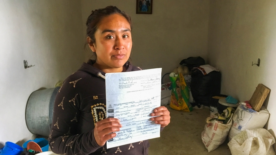 Young woman in plain room, dirt floor, holding birth certificate