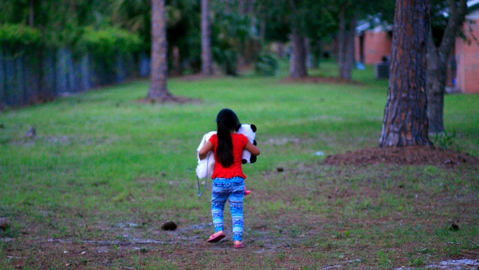 Young girl walking on lawn, holding teddy bears