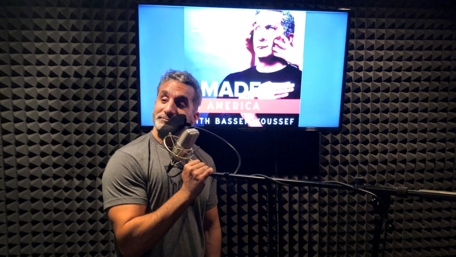 "Bassem Youssef stands in front of a microphone in a recording studio. Behind him is a screen lit up with the title of his new podcast: ""Remade in America with Bassem Youssef."""