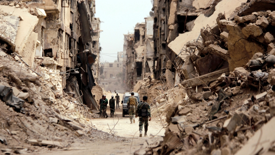 Men in camouflague fatigues walk down a street lined with rubble from destroyed buildings.