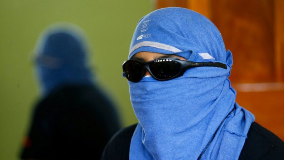 A man wearing sunglasses and a blue T-shirt around his head speaks