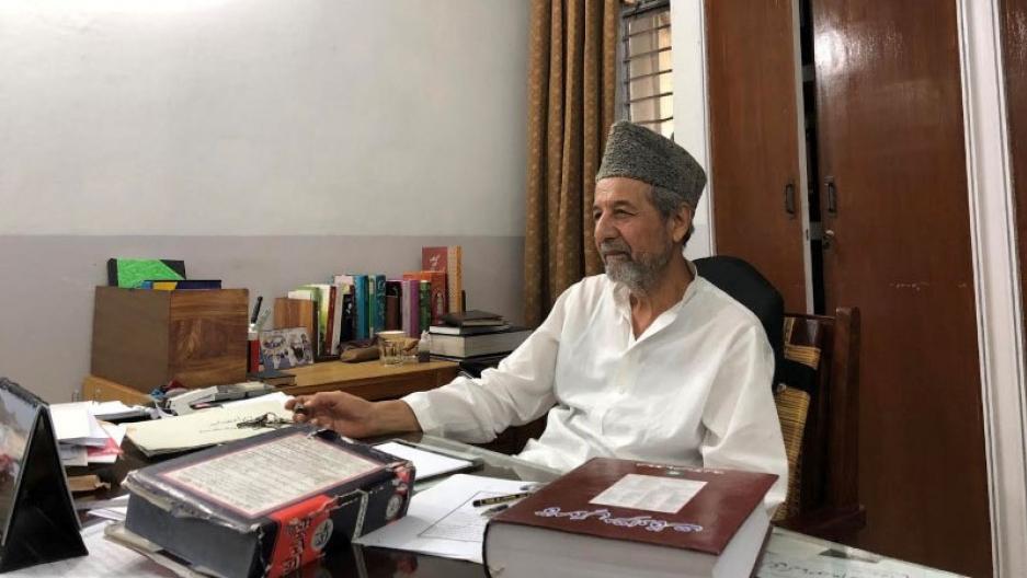 A man sits behind a desk