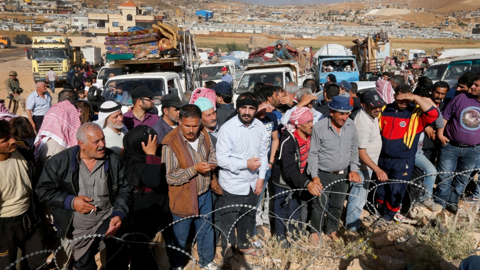 People stand at a line behind a barbed wire fence. Behind them is a line of trucks laden with mattresses and other supplies.