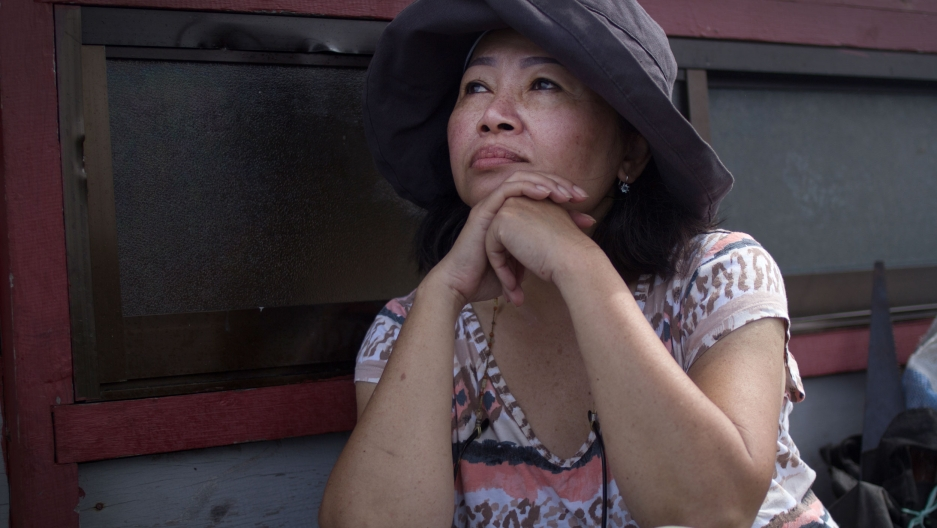 A woman wearing a brown hat sits against a wooden wall with her hands folded under her chin