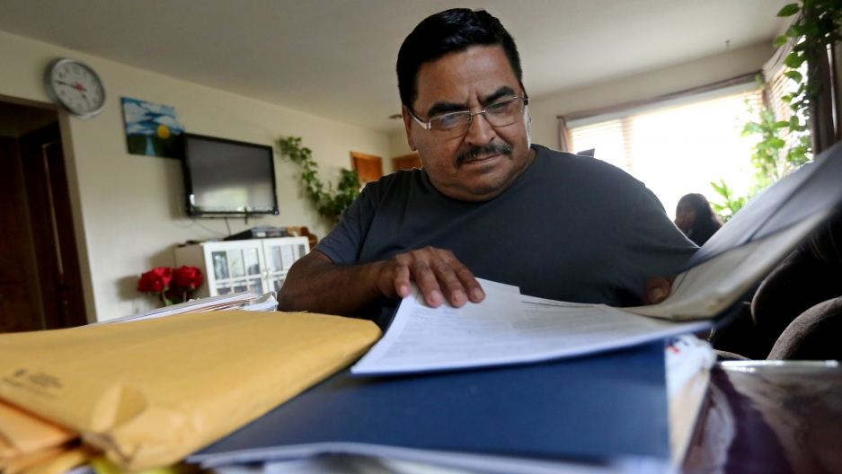 Man sits behind large stack of papers, brown envelopes
