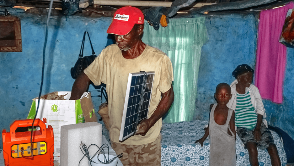 "a farmer living in Chansolme, shows off the solar-powered lighting equipment he purchased in November through the government's ""Ma Maison Eclairée"" initiative."