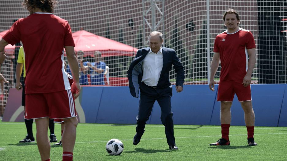 russian president vladimir putin kicks a soccer ball