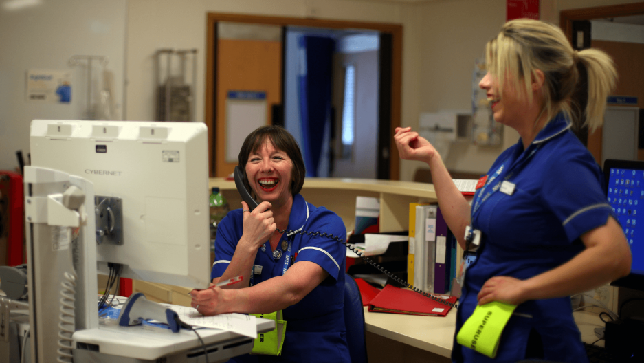 two nurses laugh at a work station in a hospital