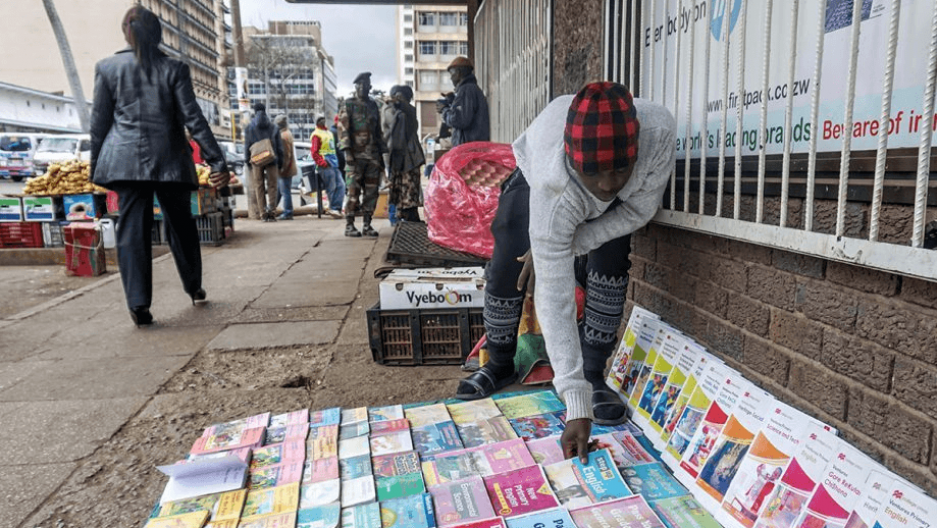 Darlington Chindoko, 22, sells textbooks on a street in Harare, Zimbabwe's capital city. The books are scarce in public schools so many parents buy them for their children.