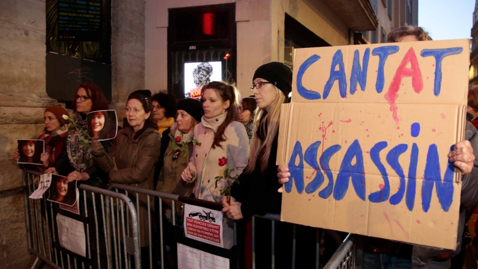 "A crowd stands behind a metal gate. One holds a sign that says ""Cantat assassin"""