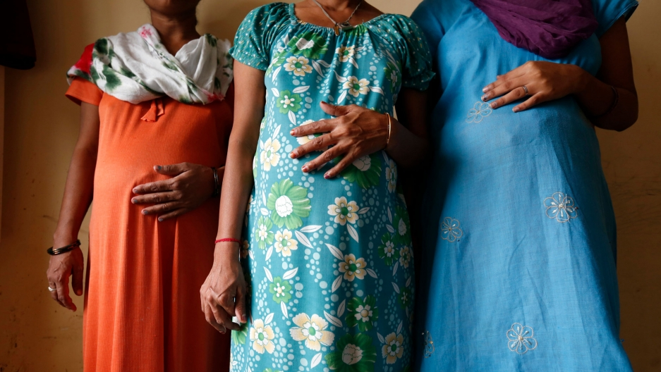 Three women stand in a line with their hands on their visibly pregnant stomachs. Their faces are cropped out of the image.