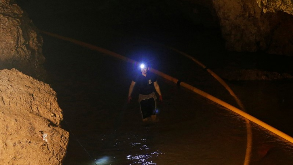 A diver walks in Tham Luang cave complex wearing waders and a headlamp.
