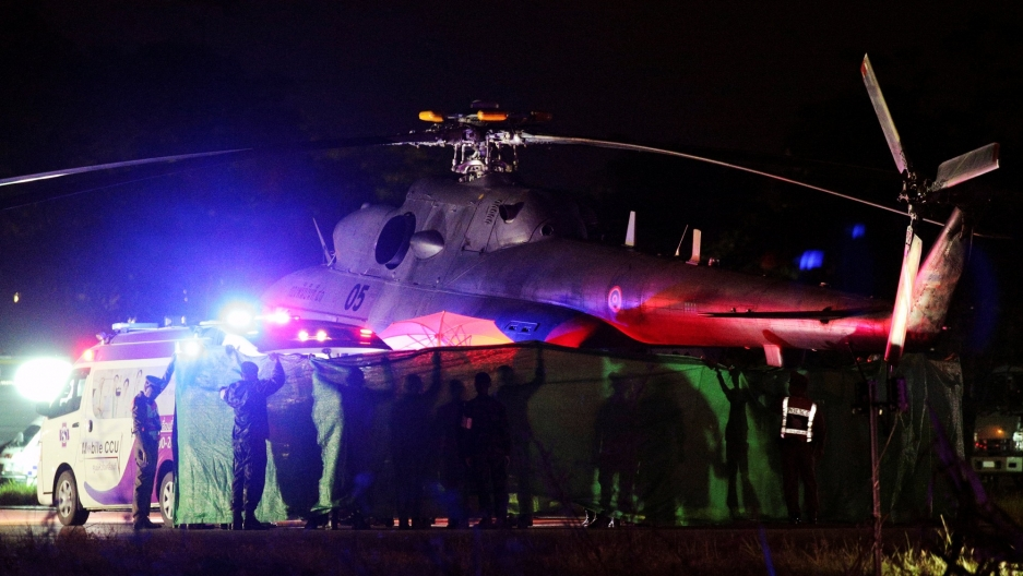 A military helicopter is shown in a photograph taken at night in Chiang Rai, Thailand.