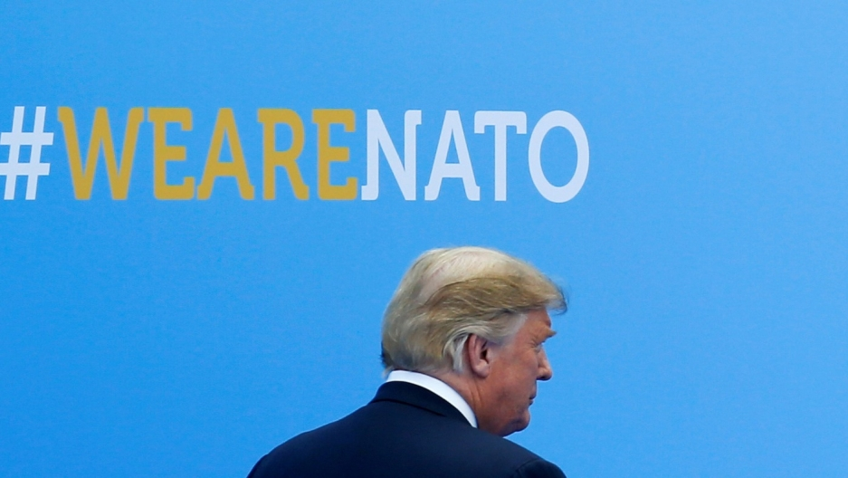 US President Donald Trump walks past a blue wall with #wearenato printed on it.