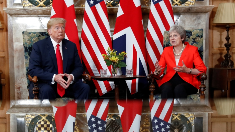 US President Donald Trump is show sitting next to British Prime Minister Theresa May at the end of a table with flags behind them.