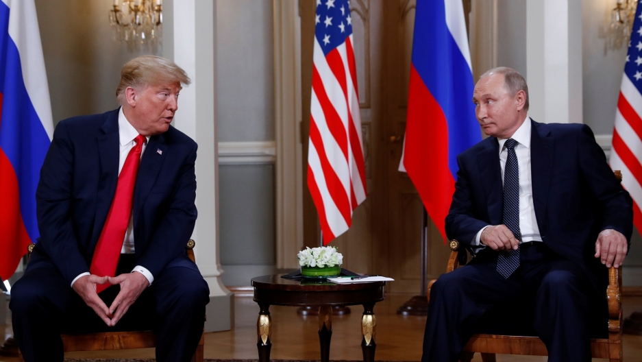 US President Donald Trump and Russia's President Vladimir Putin are shown seated in wooden armchairs with flags behind them in Helsinki, Finland, July 16, 2018.