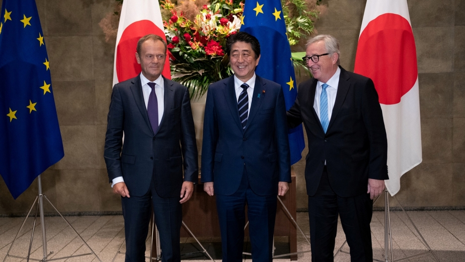 Japanese Prime Minister Shinzo Abe stands along side European Commission President Jean-Claude Juncker and European Council President Donald Tusk with EU and Japan flags behind them.