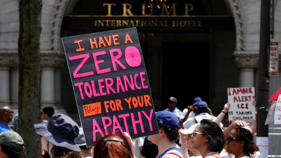 "An immigration activist is shown carrying a sign that reads, ""I have zero tolerance policy for your apathy,"" outside the Trump International Hotel in Washington, DC, June 30, 2018."
