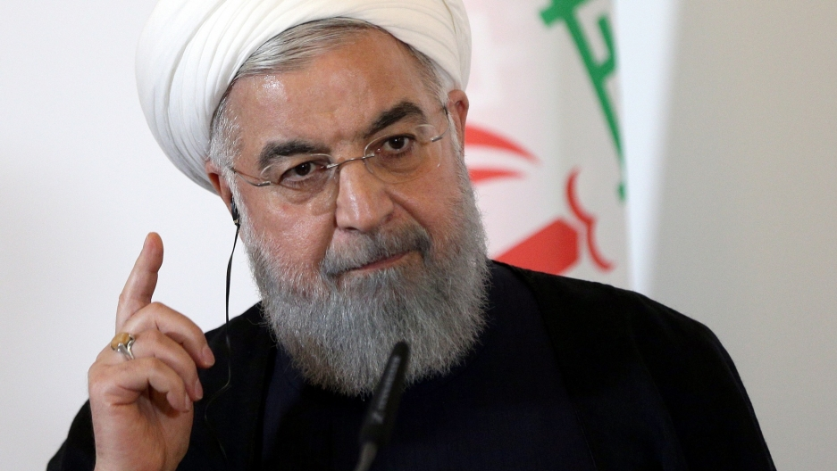 Iran President Hassan Rouhani with his right hand raised and finger pointed upward.