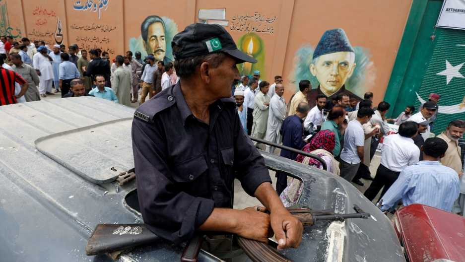 A security officer is seen perched through a vehicle's sun roof as electoral workers stand in line along a wall in Karachi, Pakistan.
