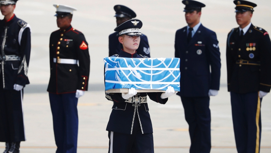 A uniformed soldier carries a casket containing the remains of a US soldier draped in a blue flag.