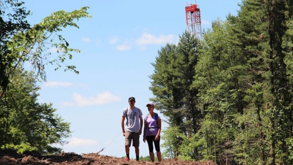 Kenton Ganster, left, stands with his mother, Kathleen, with a drilling rig used for fracking visible in the background off of the Rachel Carson Trail north of Pittsburgh.