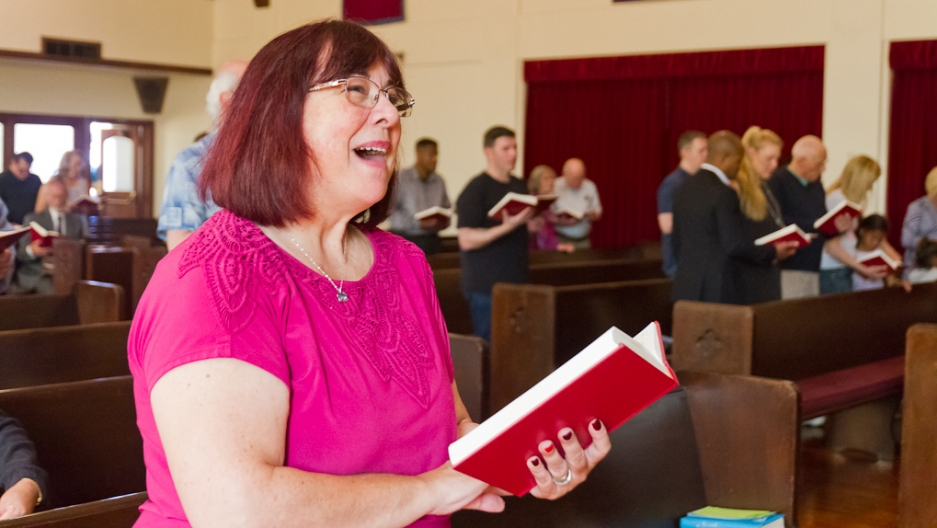 Woman in church holding book and singing