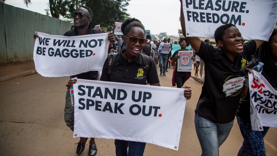 Men and women are walking in the streets of Kampala holding placards with messages in support of women's rights.