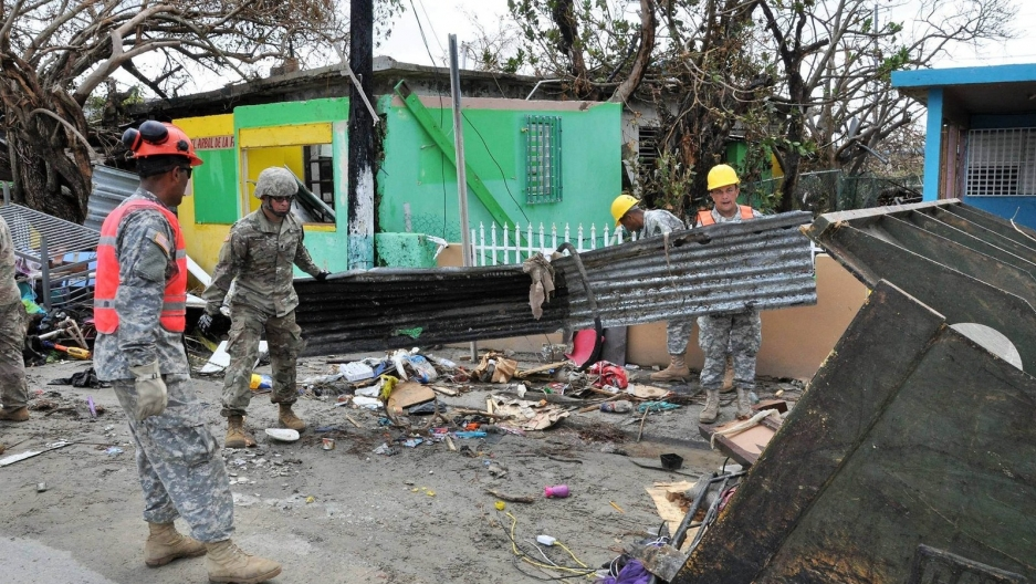 Soldiers of the Puerto Rico National Guard and volunteers of the Puerto Rico State Guard clear a road at Punta Santiago in Humacao, Puerto Rico. Scenes of utter devastation were found throughout the island after Hurricane Maria hit last September.