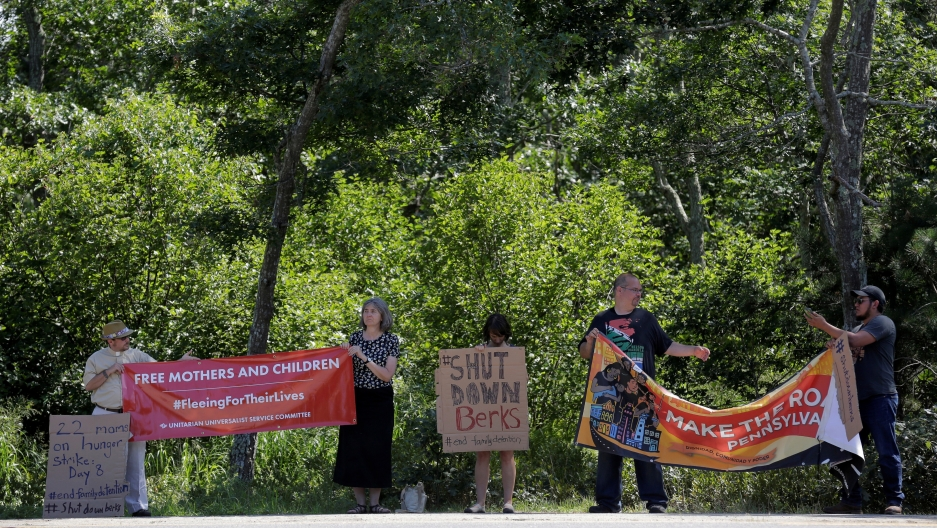 "People stand on side of road in front of trees holding signs; one reads ""Shut Down Berks"""