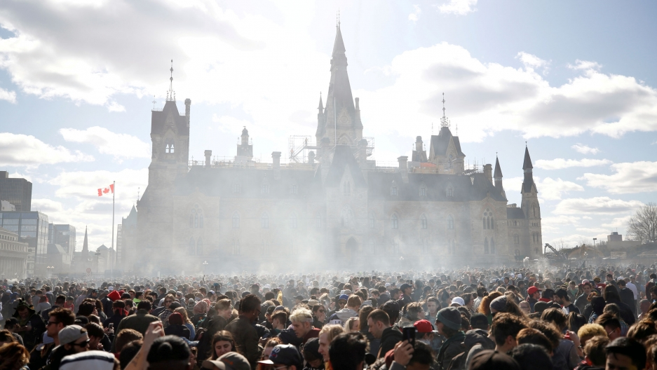 Smoke rises above a crowd assembled in front of the Ottawa government building