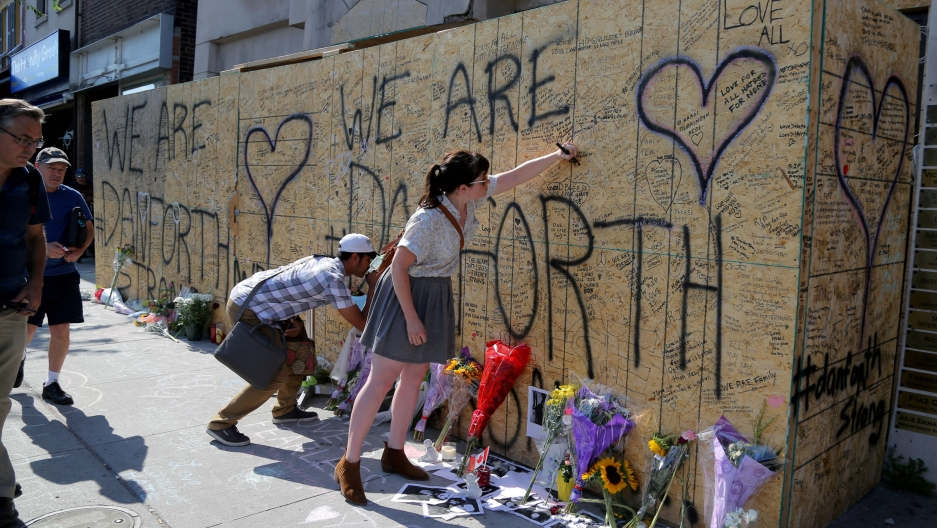 "People leave messages, flowers and other trinkets on a plywood wall that says ""We are Danforth"""