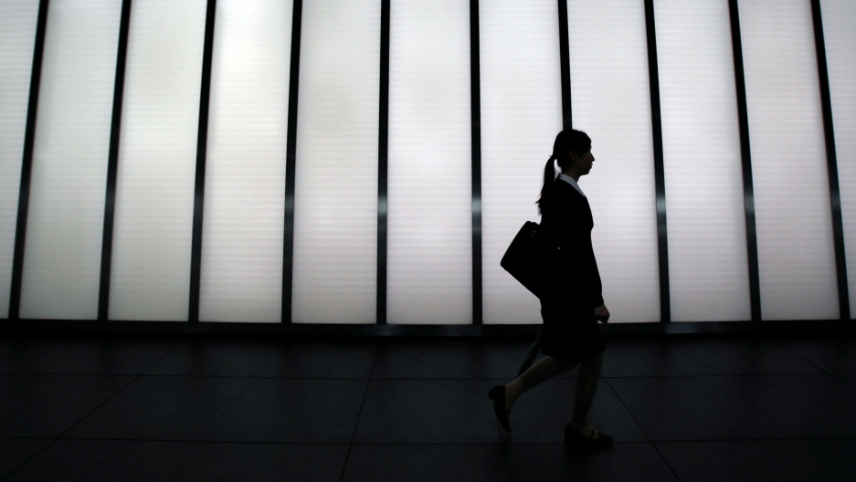 A woman in a business suit is silhouetted against a bright building