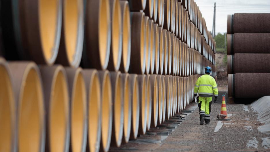 a worker walks alongside an oil pipeline